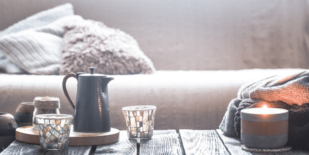 Foto de still life from home interior on a wooden background with a candle and a small kettle with a beautiful glass, home comfort concept - Imagen libre de derechos
