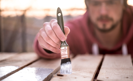 Photo pour A man paints with white paint on wooden planks. Man in industrial concept. There is a place for text, the object is close up - image libre de droit