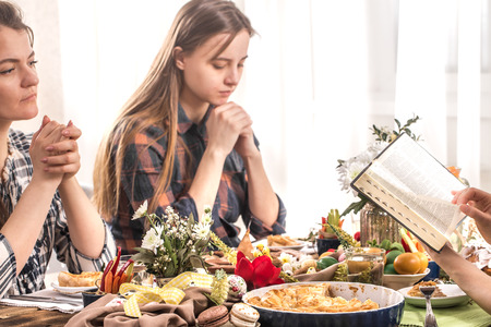 Photo for Home Holiday friends or family at the festive Easter table make a prayer before eating, the concept of celebration - Royalty Free Image