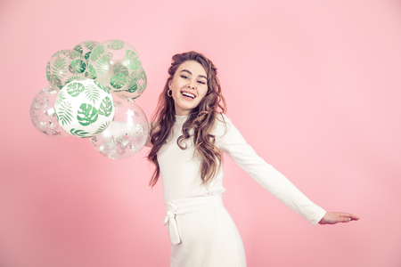Photo pour Young girl with balloons in a tropical print on a colored pink background, dressed in a beautiful white dress, the concept of women's day and holiday - image libre de droit