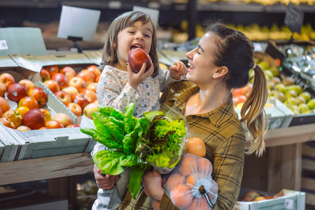 Foto für Family in the supermarket. Beautiful young mom and her little daughter smiling and buying food. The concept of healthy eating. Harvest - Lizenzfreies Bild