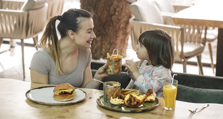 Photo for Loving family. Mom with cute daughter eating fast food in a cafe, family and nutrition concept - Royalty Free Image