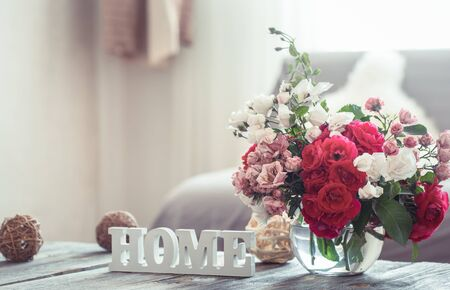 Foto de Still-life with an inscription house and a vase with flowers of different roses. The concept of home comfort and decor. - Imagen libre de derechos