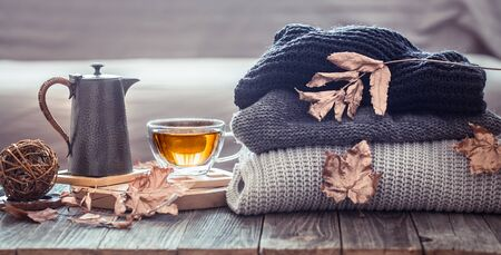 Foto de Cozy autumn still life with a cup of tea and decor items in the living room. Home comfort concept - Imagen libre de derechos