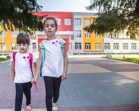 Foto de Back to school education concept with girl kids, elementary students, carrying backpacks going to class on school first day holding hand in hand together walking up building stair happily - Imagen libre de derechos
