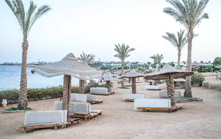Photo pour Empty beautiful beach with umbrellas and sunbeds in Egypt . the concept of travel and recreation . - image libre de droit