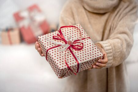 Photo pour A woman in a warm sweater, holding a beautiful Christmas gifts. Holiday concept. Close up. - image libre de droit