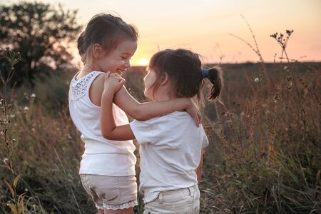 Foto de Two little sisters hugging in a field at sunset . Dressed in white. The concept of family values and friendship . - Imagen libre de derechos