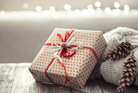 Foto de Cozy Christmas background on a wooden background with a gift and Christmas decor items in a homely atmosphere. - Imagen libre de derechos