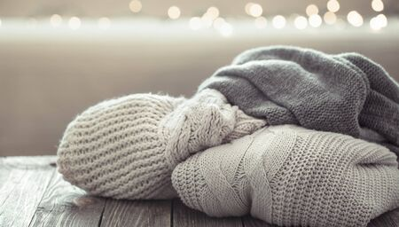 Photo pour A cozy stack of knitted sweaters on a wooden background . Close up. - image libre de droit