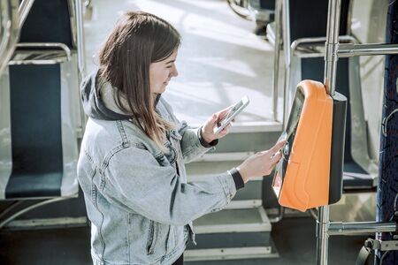 Photo pour A young woman contactless pays for public transport. Payment by card, Bank transfer . - image libre de droit
