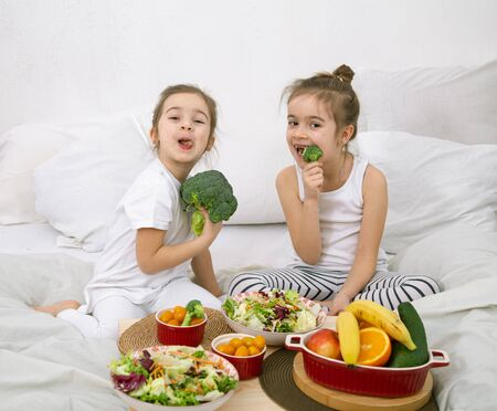 Photo pour Healthy food at home. Happy two cute children eating fruits and vegetables in the bedroom on the bed. Healthy food for children and teenagers. - image libre de droit