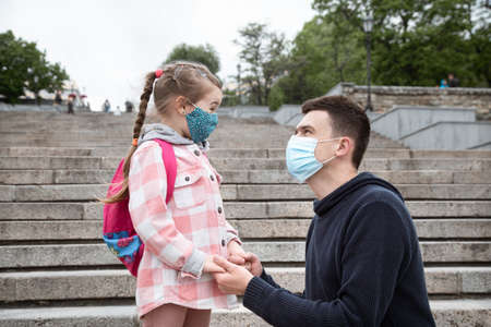 Photo pour Back to school, pandemic. Father and daughter in a mask. Friendly family relationships. Education - image libre de droit