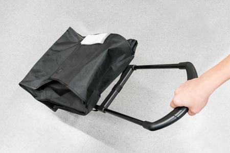 Foto de Woman hand holding black travel bag against grey background - Imagen libre de derechos