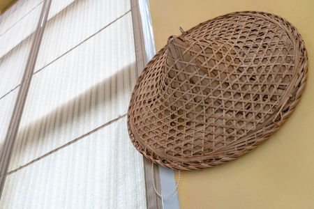 Foto de Traditional hat made of bamboo wood and dry leaves hanging on yellow wall background. - Imagen libre de derechos