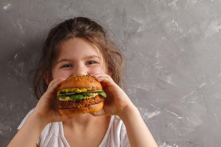 Photo pour The little girl is eating a healthy baked sweet potato burger with a whole grains bun, guacamole, vegan mayonnaise and vegetables. Child vegan concept - image libre de droit