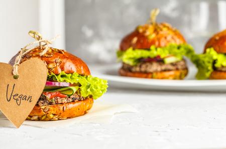 Photo pour Vegan bean burgers with vegetables and tomato sauce on white dish, copy space. Healthy vegan food concept. - image libre de droit