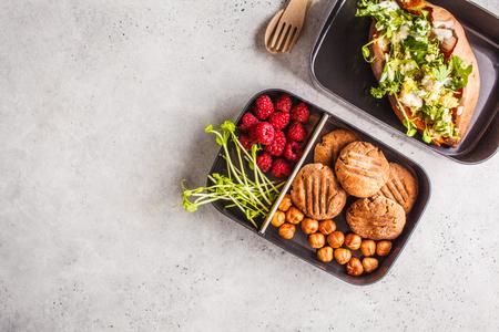 Foto de Healthy meal prep containers with quinoa Stuffed Sweet Potatoes, cookies, nuts and berries, overhead shot with copy space. - Imagen libre de derechos