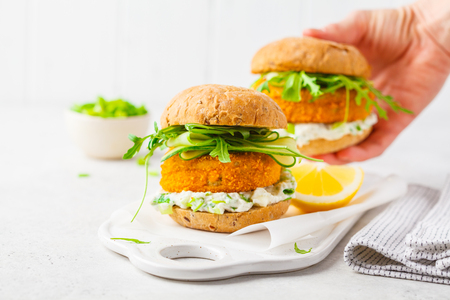 Photo pour Fish burger with cucumber, arugula and mayonnaise sauce, white background, vegetarian food. - image libre de droit