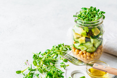 Photo pour Green salad with chickpeas in a jar, white background, copy space. Detox, vegan food, plant based diet concept. - image libre de droit