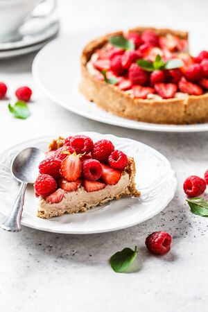 Photo pour Vegan berry tart with raspberries, strawberries and cream on a white plate. - image libre de droit