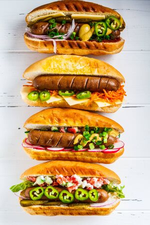 Foto de Hot dogs with different toppings on a white background. Fast food concept. - Imagen libre de derechos