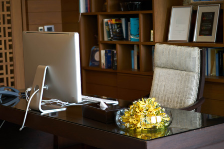 Room office of Manager or headmaster include computer armchair vase.