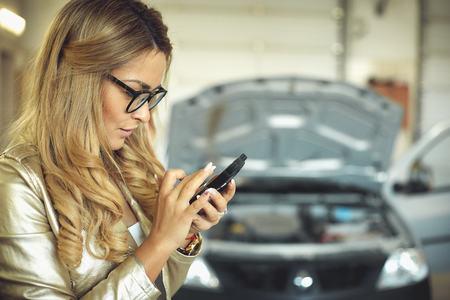 Foto de beautiful young blonde woman in glasses is calling on the phone and auto mechanic for auto repair - Imagen libre de derechos