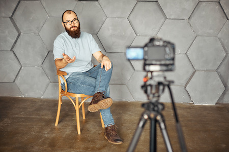 Photo for content creation for social media. bearded man shooting video of himself using camera on tripod. modern technology and blogging freelance work concept - Royalty Free Image