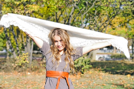 The young beautiful girl in autumn wood with a white woolen scarf