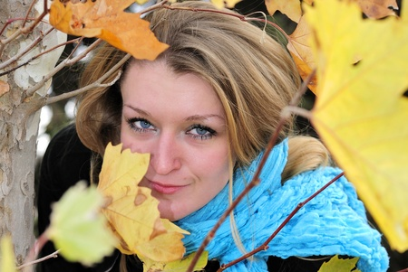 The young beautiful girl in autumn wood among yellow leaves