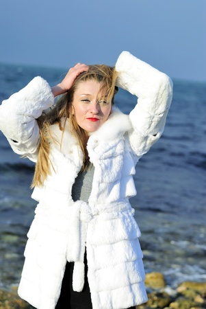 The young beautiful girl in a white fur coat with red lipstick