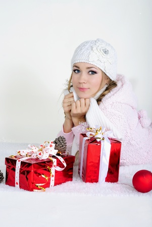 The young beautiful girl in a white cap with New Year's gifts