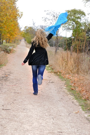 The young beautiful girl runs in autumn wood with a scarf in hands