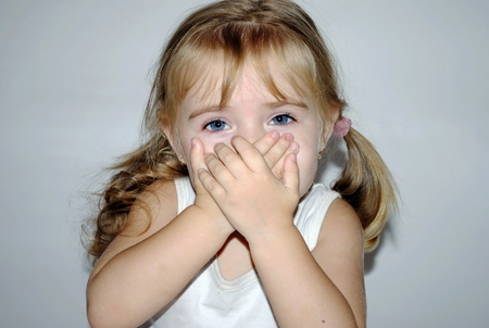 small beautiful girl has closed mouth a hand