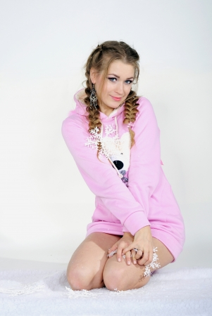 The young beautiful girl in a pink jacket with wings on a white background