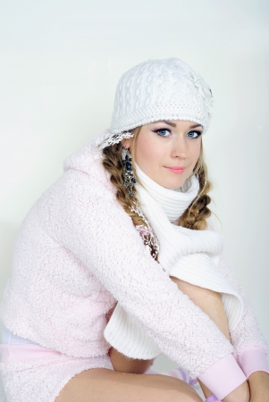 The young beautiful girl in a white cap and a scarf on a white background