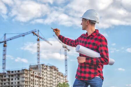 Photo pour civil engineer in a white helmet on the background of houses under construction. - image libre de droit