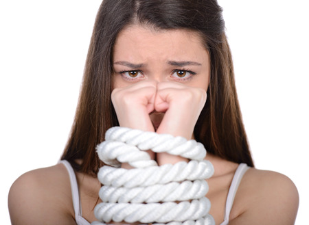 Young woman with tied up hands over white background