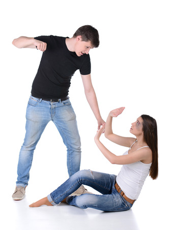 Brutal man attacking a woman. Woman protecting her face with hands