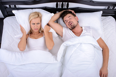 Young woman cannot sleep through the snoring of her husband in bedroom