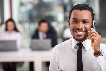 Photo pour Portrait of happy smiling customer support phone operator at workplace. - image libre de droit