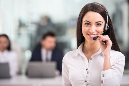 Portrait of happy smiling female customer support phone operator at workplace.