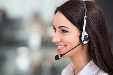 Foto de Close-up, side view of attractive young woman is working in a call center. - Imagen libre de derechos