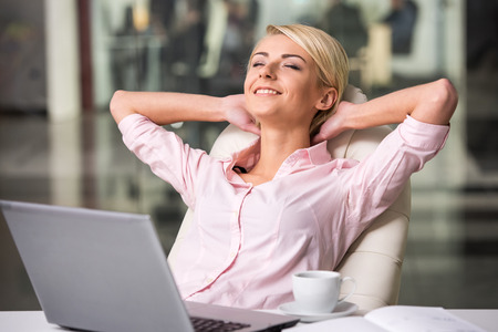 Photo for Young beautiful businesswoman is relaxing at office. - Royalty Free Image
