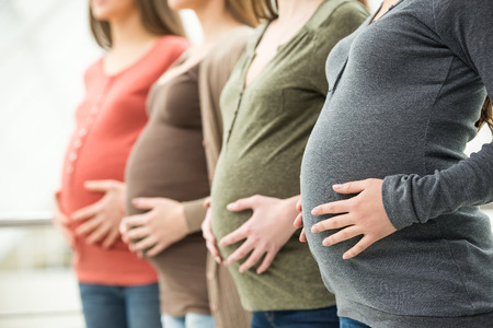 Side view of three pregnant women are touching their bellies with hands. Maternity concept.の写真素材