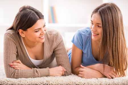 Photo pour Smiling mother and her teen daughter are lying on the floor and looking at each others. - image libre de droit