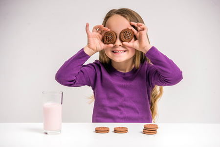 Cute little girl holding cookie while sitting at the table on grey .