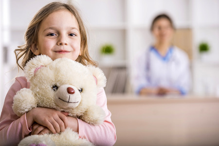 Photo pour Little girl with teddy bear is looking at the camera. Female doctor on background. - image libre de droit