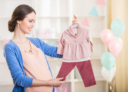Beautiful pregnant woman is looking at the baby clothes.の写真素材